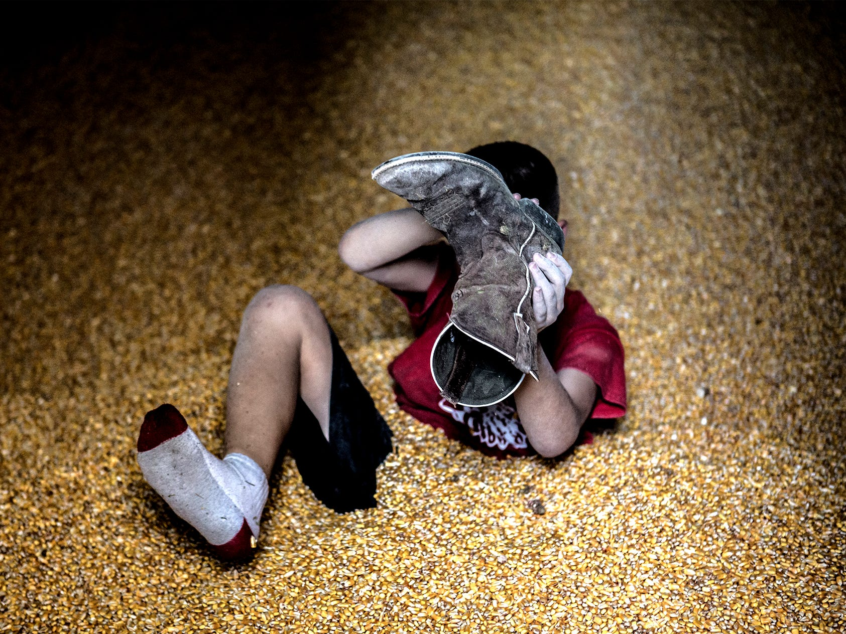 Bryce Hollenback dumps dried corn kernels out of boot after playing in the grain bin while his mom, not pictured, carefully watched to make sure he didn't get hurt in July, 2018. Bryce lives on a the family farm with his parents Andy and Maime and his older brother Aurther. Buying the farm was always Andy's dream and he says he has been fortunate to be successful so far in the 15 years they have owned the property. This year has been a bit different, however, with the tariffs that have been imposed due to President Donald Trump's trade war with China. The Hollenback family is relatively luck though because of their diverse portfolio of crops to fall back on as soy bean prices plummet.