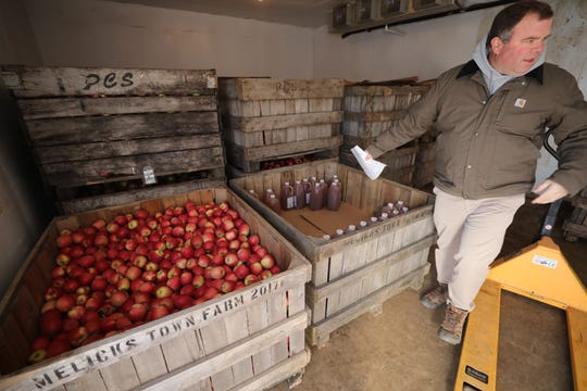 Melick's Town Farm owner John Melick stands near apples waiting to be pressed to make cider on January 11, 2019.