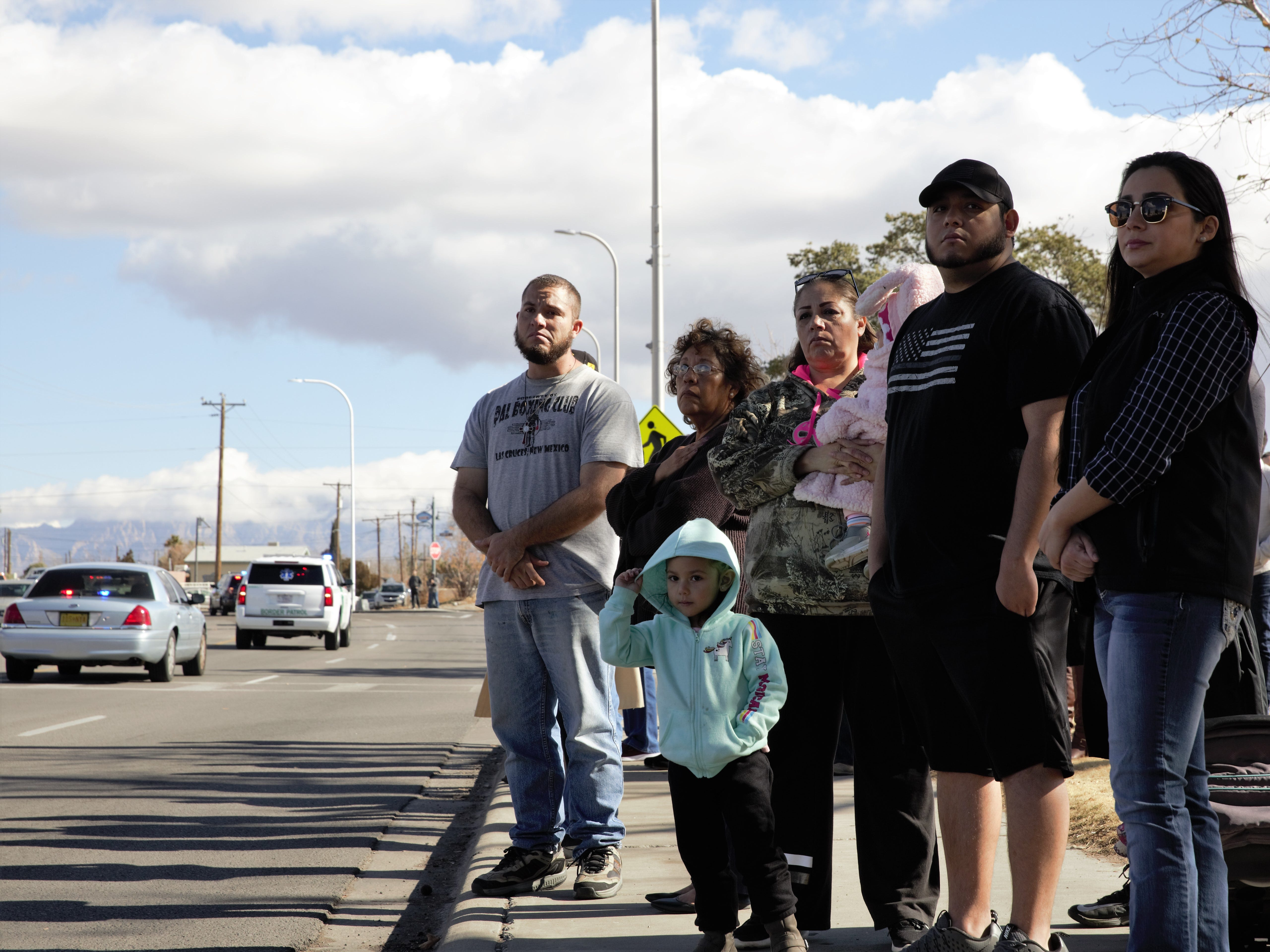 A group of well-wishers, including 3-year-old Gianelle Johnson, center, watches a funeral procession Friday, Jan. 11, 2019 for former Las Cruces Police Chief Jaime Montoya, who died from cancer recently.