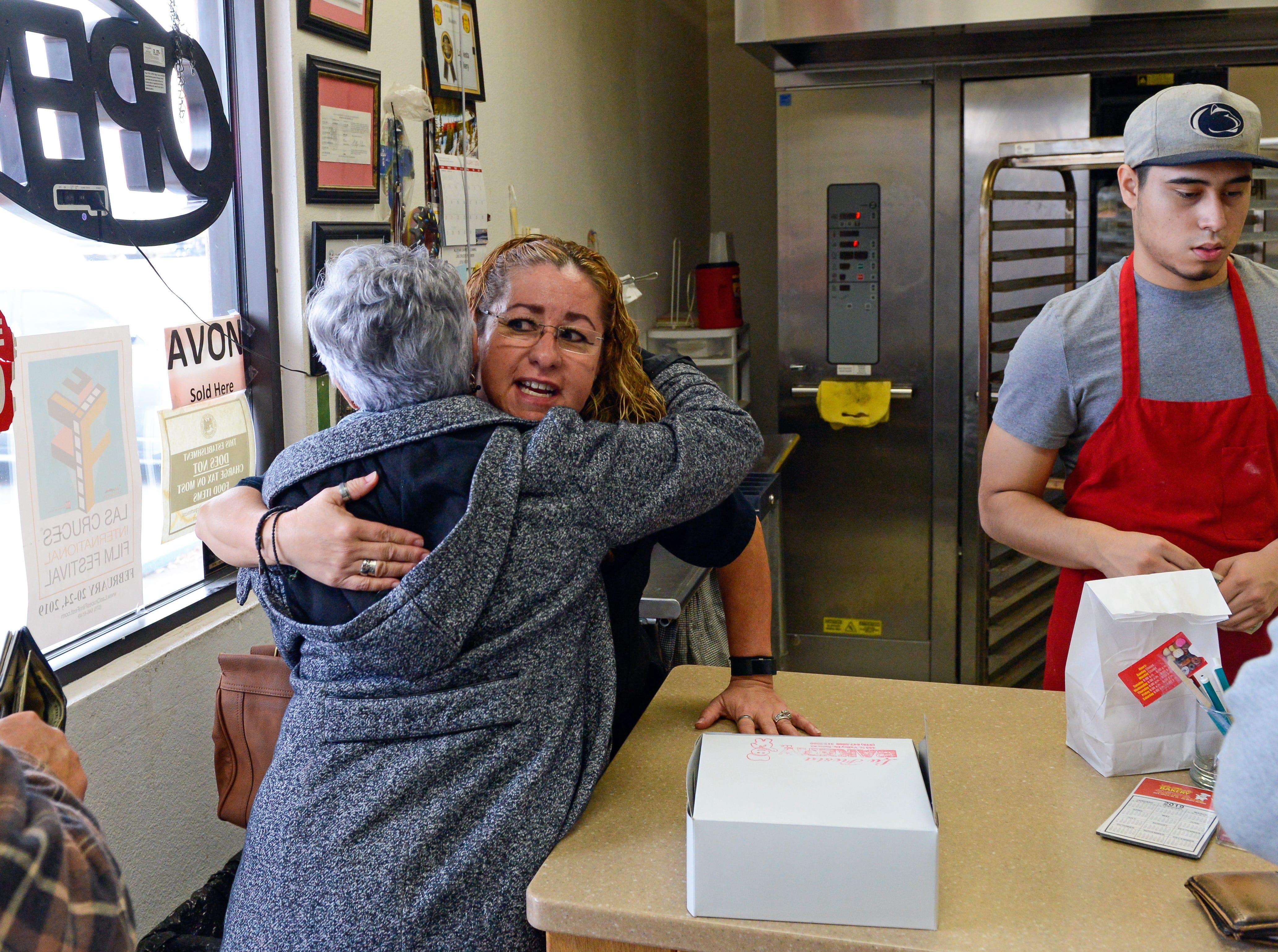 Gina Ortega, who owns La Fiesta Bakery with her husband Ray, hugs a customer at the bakery on January 10, 2019.