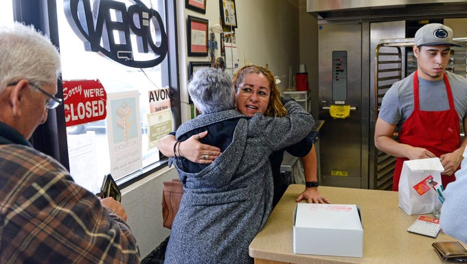 Gina Ortega, who owns La Fiesta Bakery with her husband Ray, hugs a customer at the bakery on January 10, 2019.