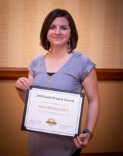 Nicole Rivera-Brastad accepts the Golden Branch Award for the New Mexico Association of Play Therapy.