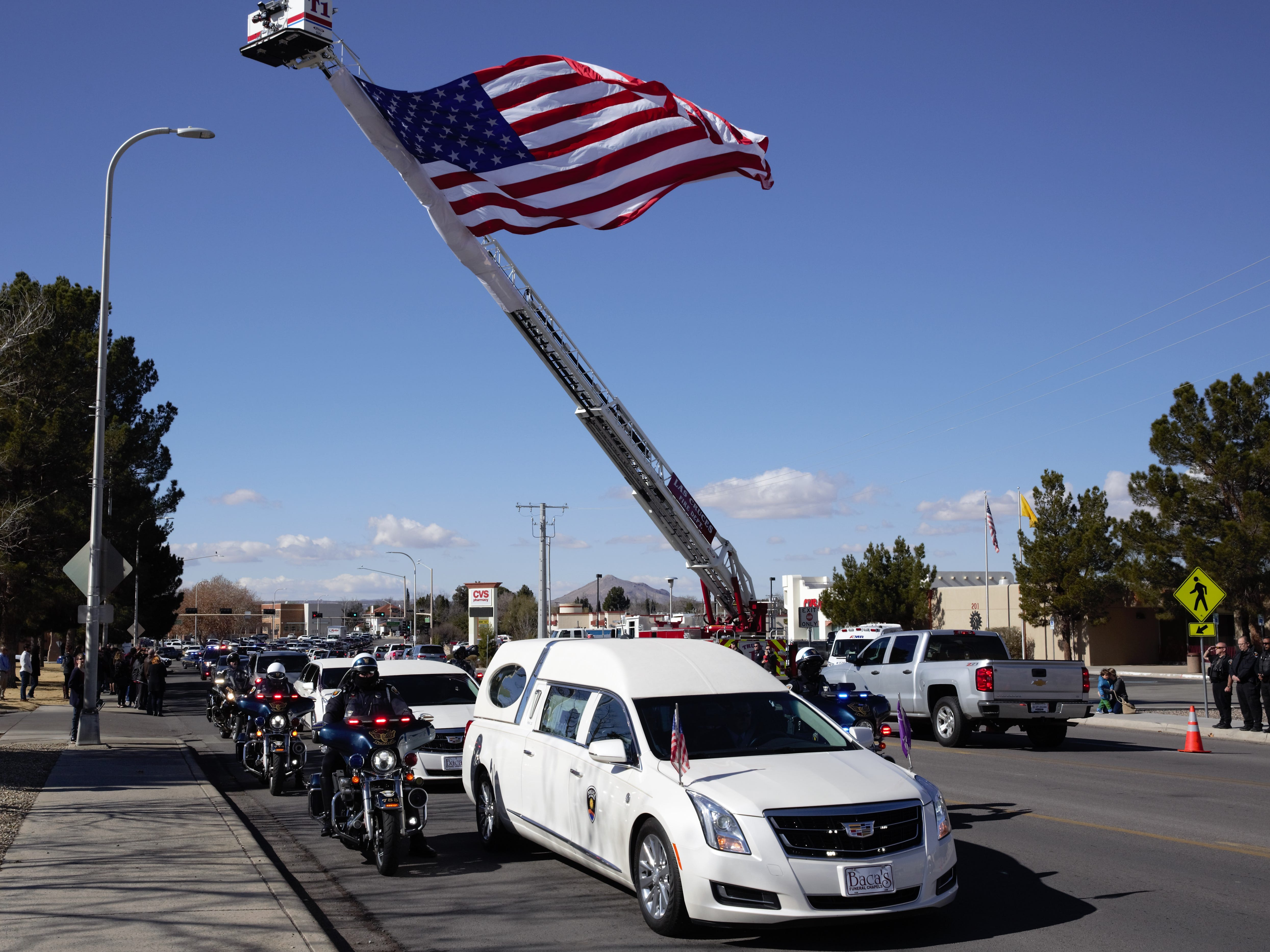 A hearse carrying late Las Cruces Police Department Chief Jaime Montoya pauses during a funeral procession past the main city police and fire stations on Picacho Avenue on Friday, Jan. 11, 2019.