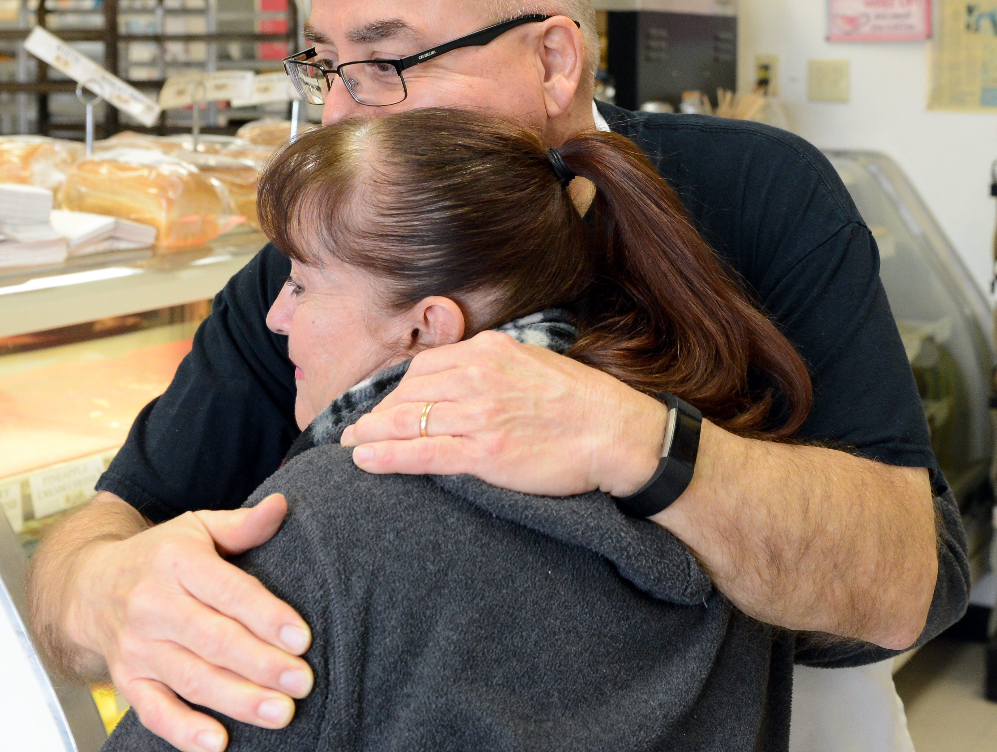 Ray Ortega, who owns La Fiesta Bakery with his wife Gina, hugs a customer at the bakery on January 10, 2019.