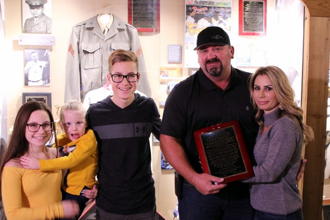 Shane Andrews and his family pose in front of his exhibit during Friday's Carlsbad Hall of Fame Induction.