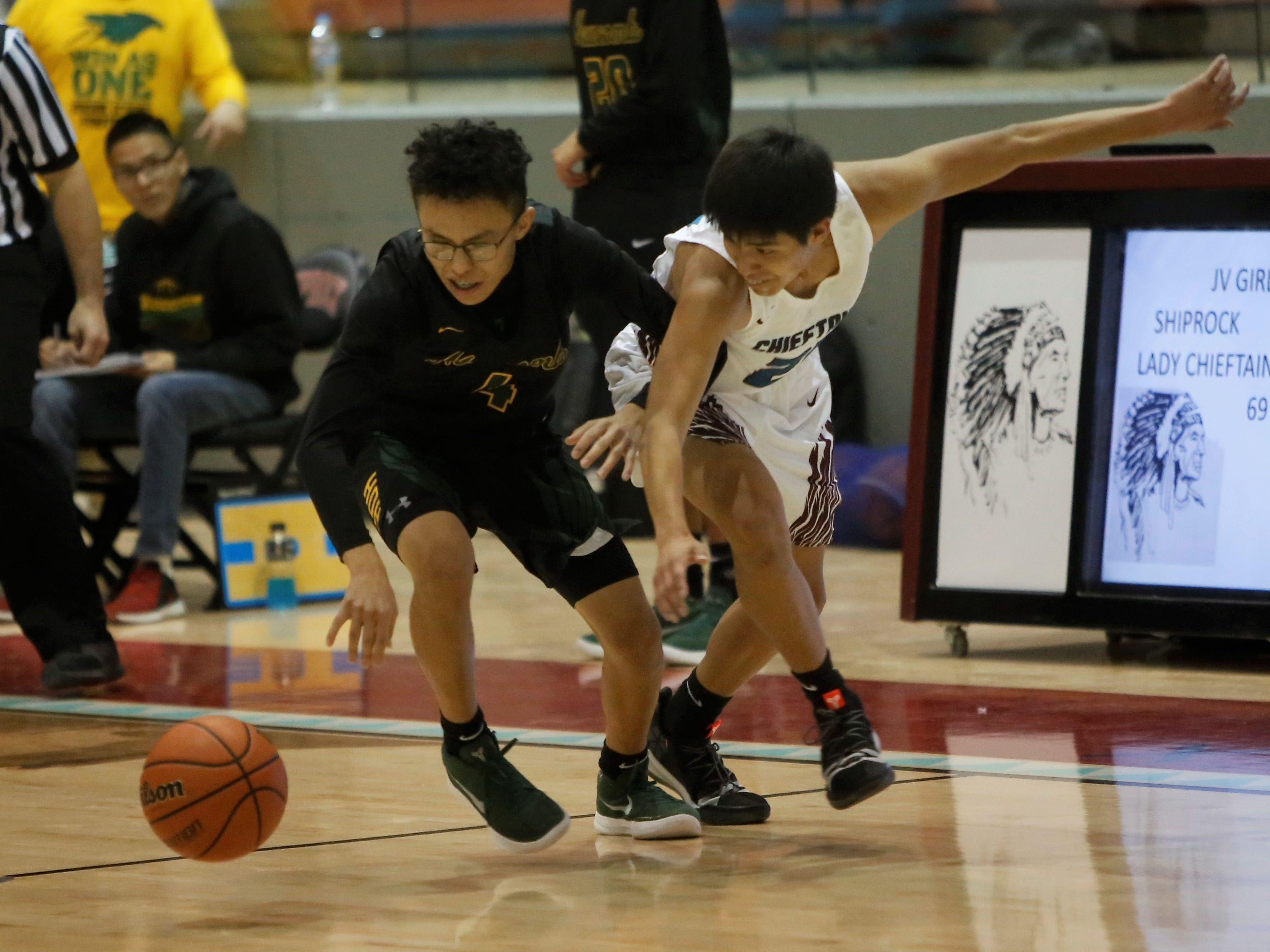 Newcomb's Jared John and Shiprock's Takobe Charley chase after a loose ball during Thursday's game at the Chieftain Pit in Shiprock.
