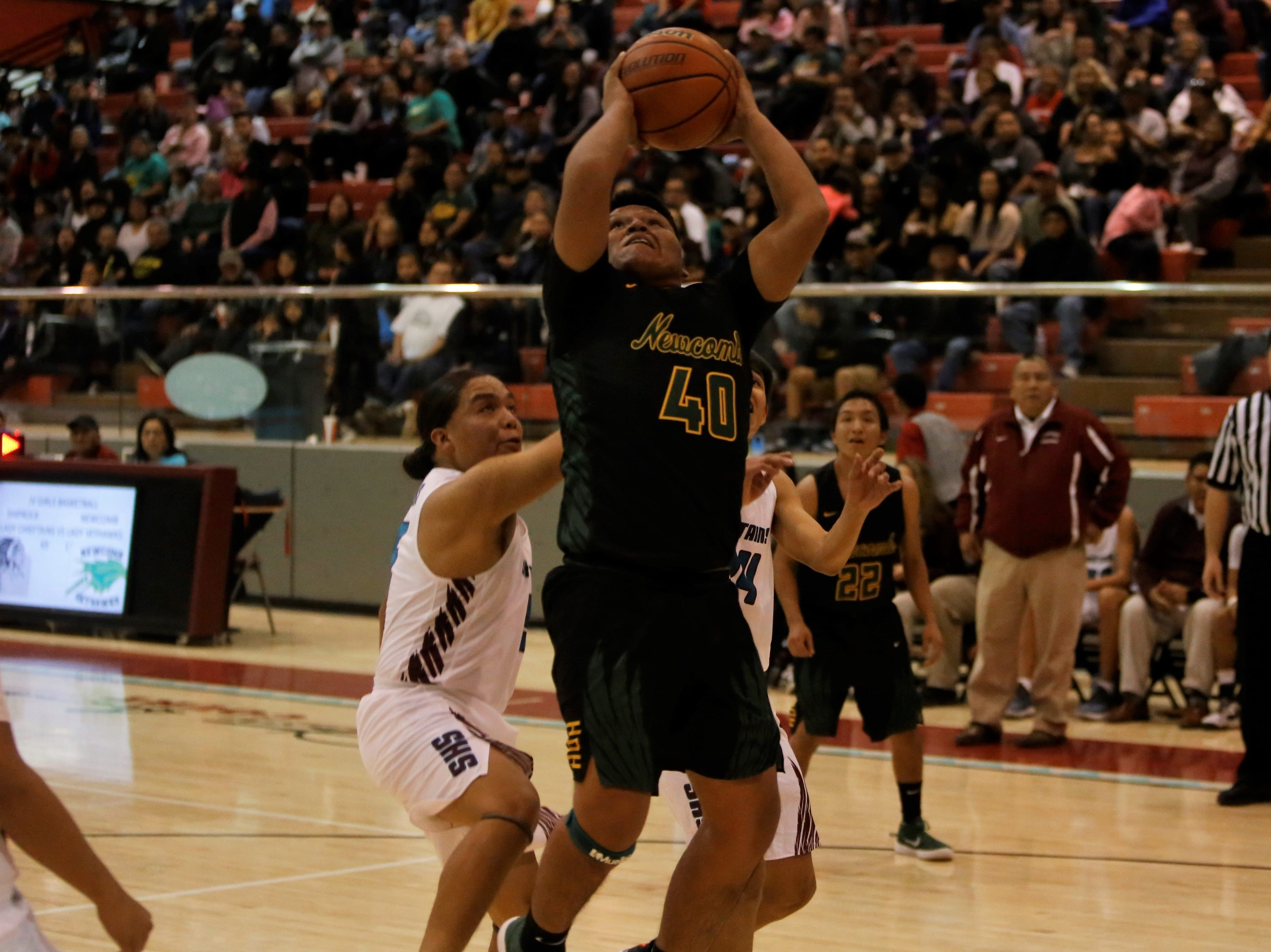 Newcomb's Tracey Bryant jumps up and makes a basket against Shiprock during Thursday's game at the Chieftain Pit in Shiprock.