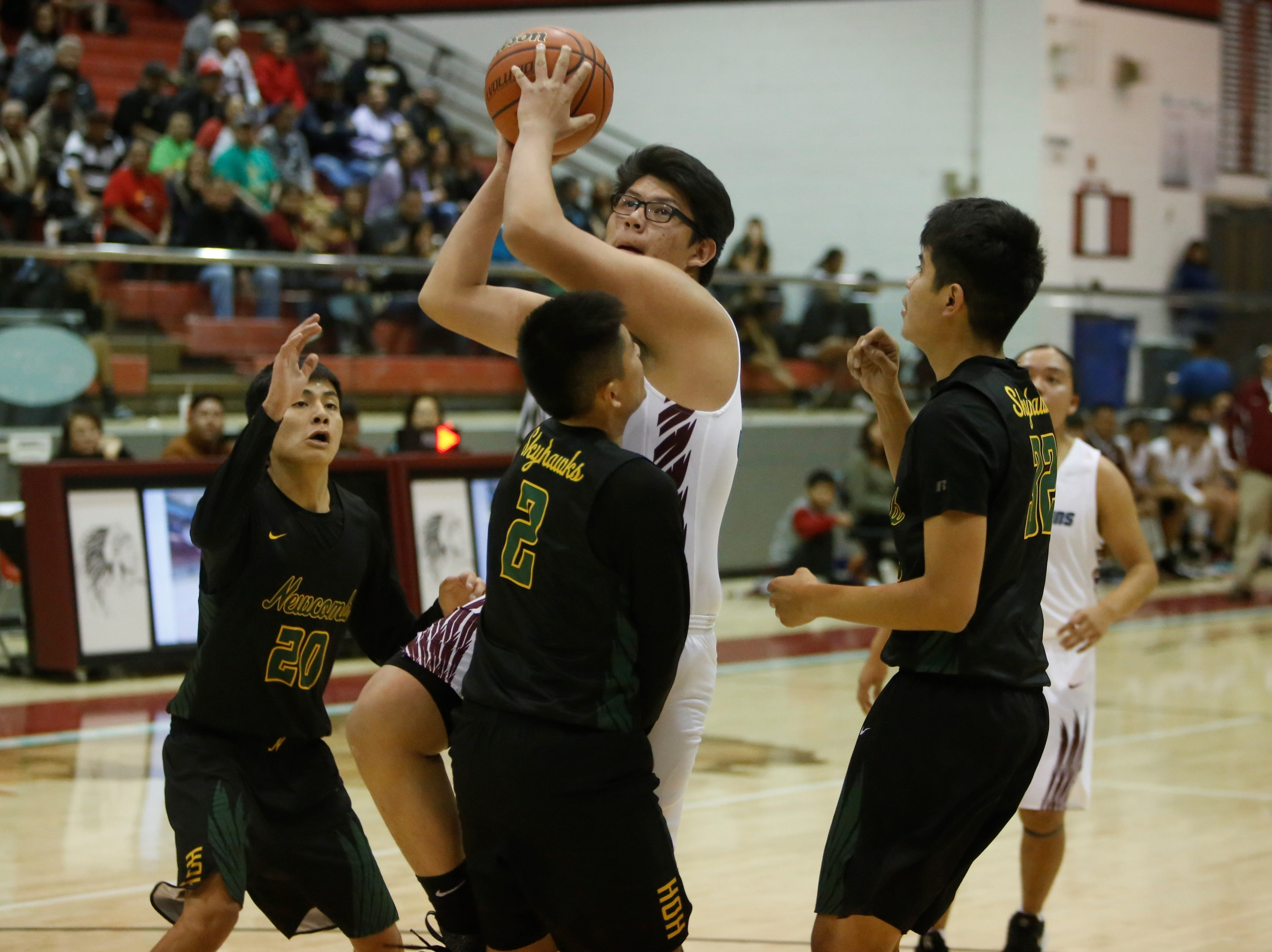 Shiprock's Eeyan John bumps into Newcomb's Deion Johnhat (2) driving to the basket for a layup during Thursday's game at the Chieftain Pit in Shiprock.