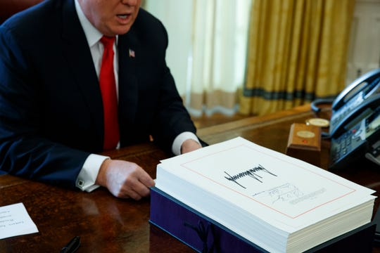 In this Dec. 22, 2017, file photo President Donald Trump speaks with reporters after signing the tax bill and continuing resolution to fund the government in the Oval Office of the White House in Washington.