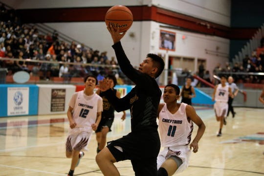 Newcomb's Deion Johnhat drives to the basket for a fast-break layup against Shiprock during Thursday's game at the Chieftain Pit in Shiprock.