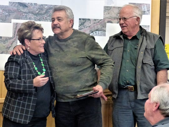 Eddie Saenz, center, gives a hug to Ruidoso Village Manager Debi Lee, as he receives his retirement plaque. At right is Forestry Department Director Dick Cooke.
