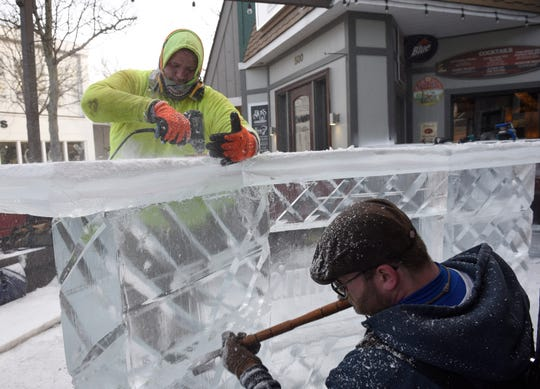 Chris Busuash and Paul Nuznov work on the ice bar at E.G. Nicks during the 2019 Plymouth Ice Festival.