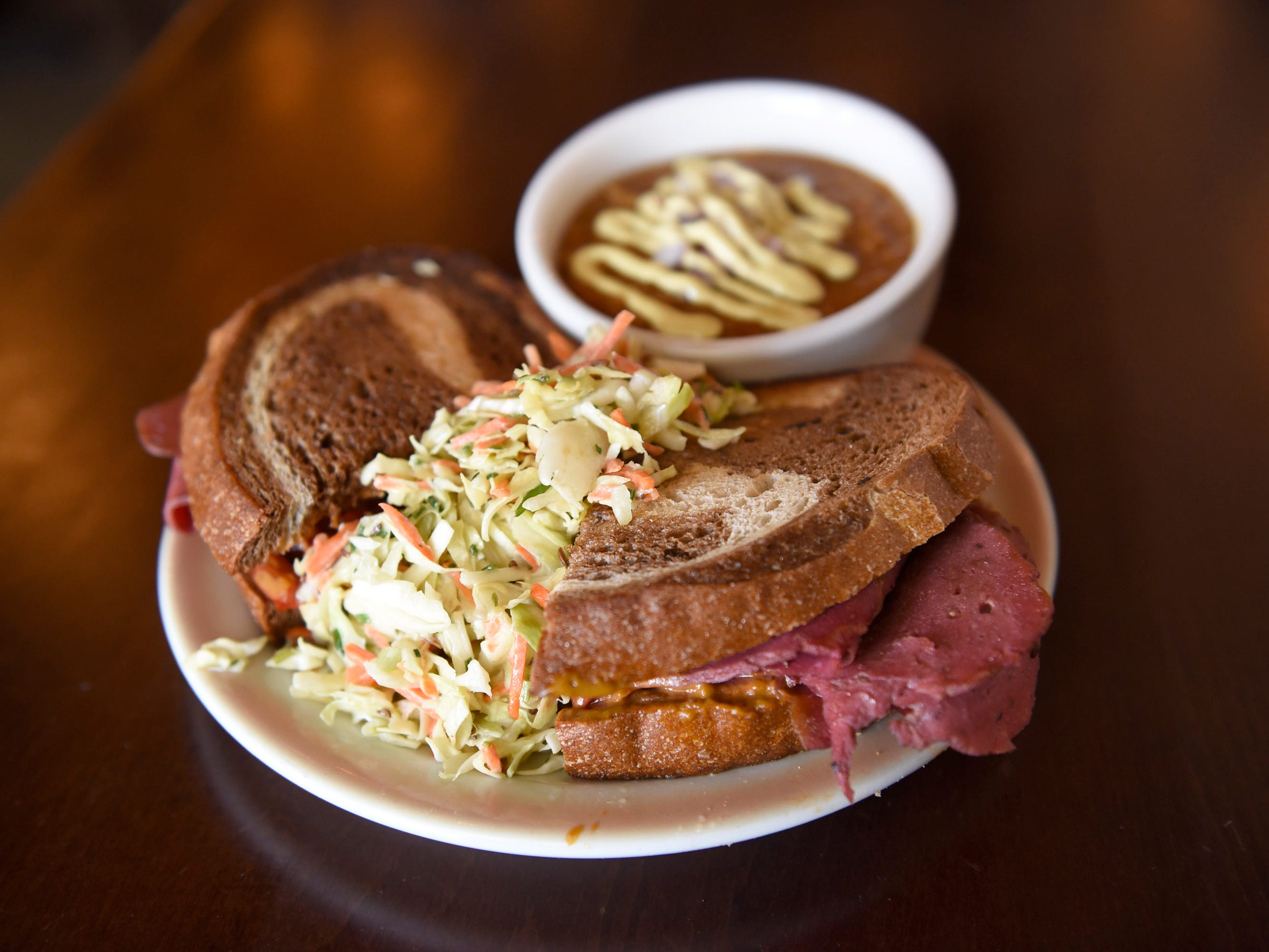 The Chive Reuben is made with corned beef seitan, cheese sauce, red peppers, caramelized onions, dill relish sauce, deli slaw and Detroit marble rye.