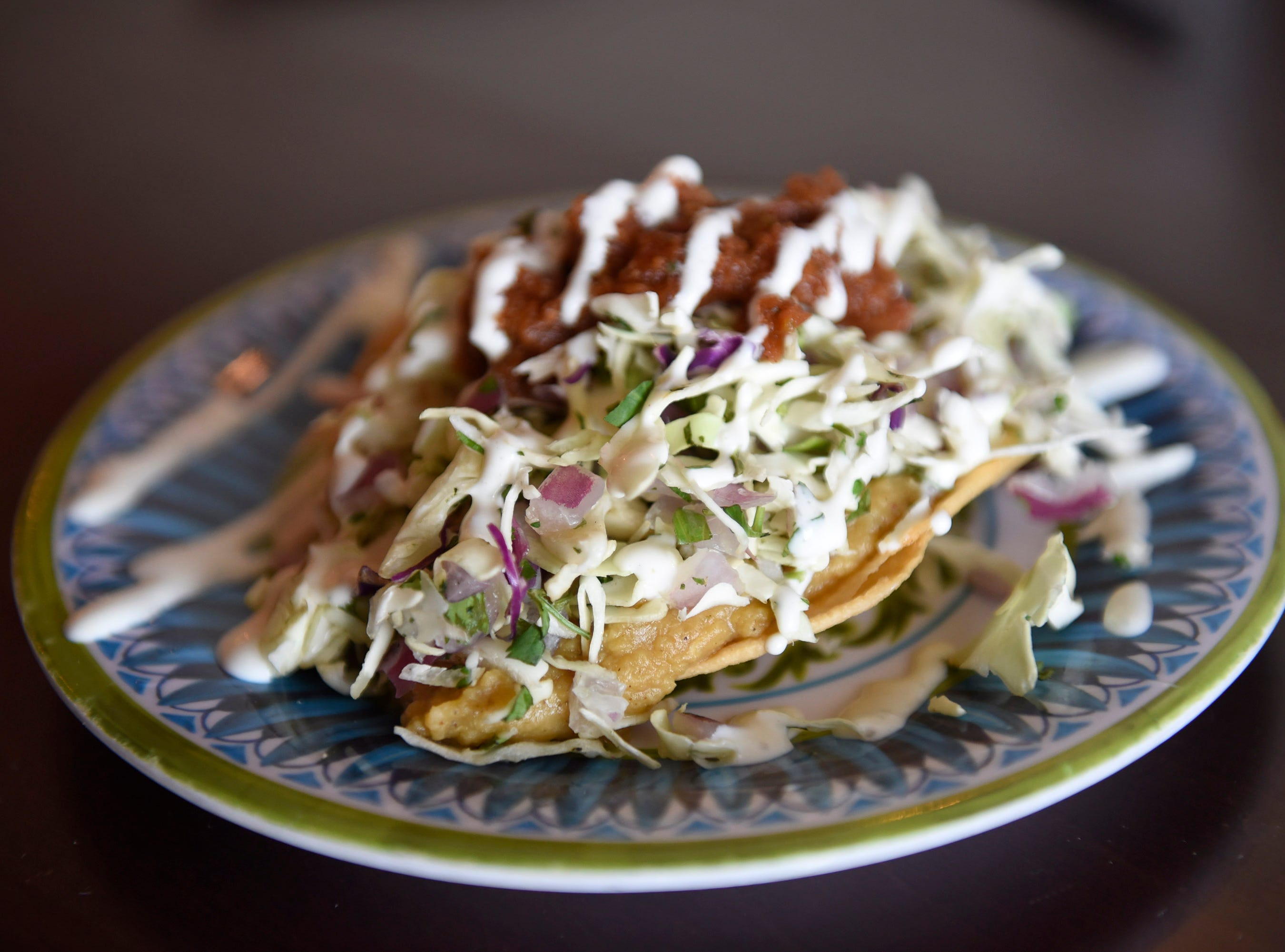 The Chive Tostada made with cumin, lentil chili, cilantro Lime Slaw, salsa, and sour cream.