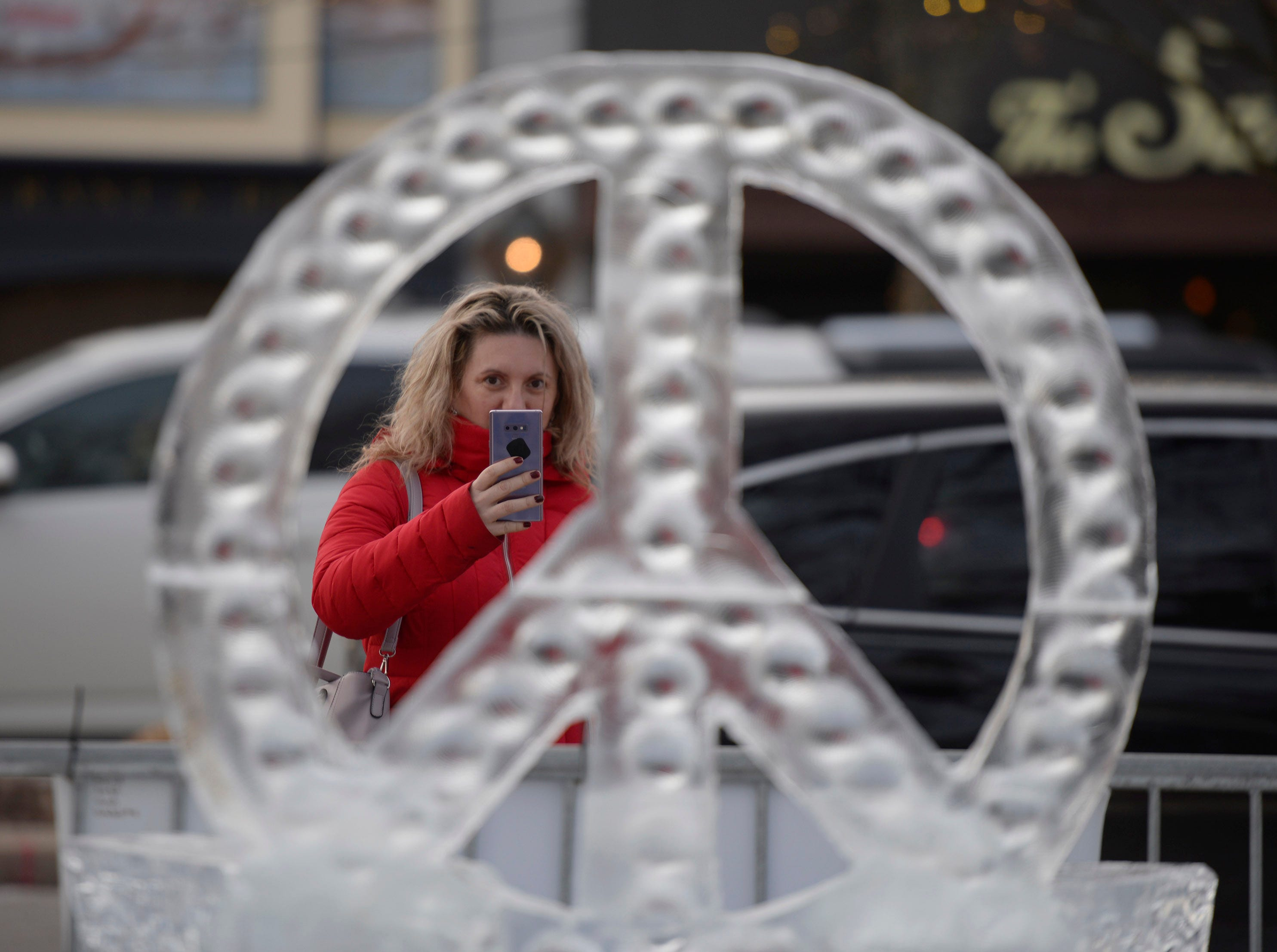 Joanna Nicoara takes a photo with her phone of one of the more than 100 ice sculptures in Kellogg Park in downtown Plymouth.