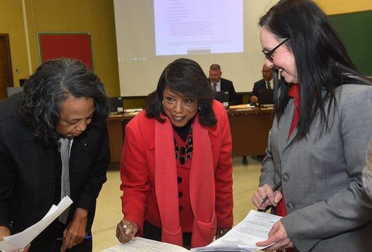 Hazel Sias, left, and Joyce Haynes sign in prior to being sworn in as St. Landry Parish School Board members, as St. Landry Parish Deputy Clerk of Court Lisa Doyle looks on.
