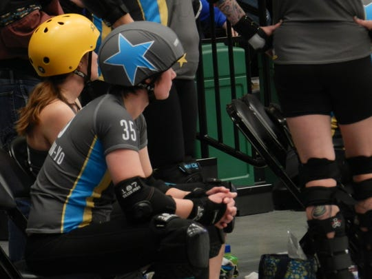 In a roller derby bout, the jammer is the person with the star on her helmet that scores points by pushing through the other team's blockers.