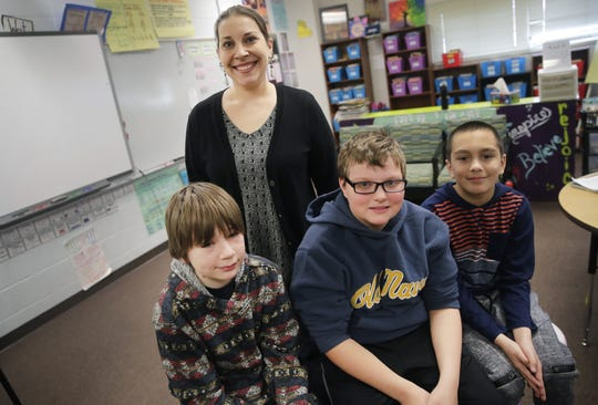 Ben Griffin (center), a fifth-grade student at Clay Lamberton Elementary School, sits for a portrait with teacher's aide Amanda Osterberg and classmates Rowan Hanson and Chad Halbesma Thursday, Jan. 10, 2019, in Berlin. The trio saved Griffin as he choked on a tater tot in the lunch room.