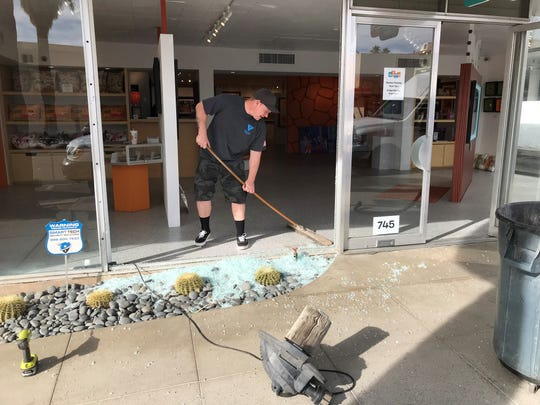Richard Sletten, of Valley Glass, cleans up the shattered remnants of the window at Shag the Store in downtown Palm Springs on Friday, Jan. 11, 2019.