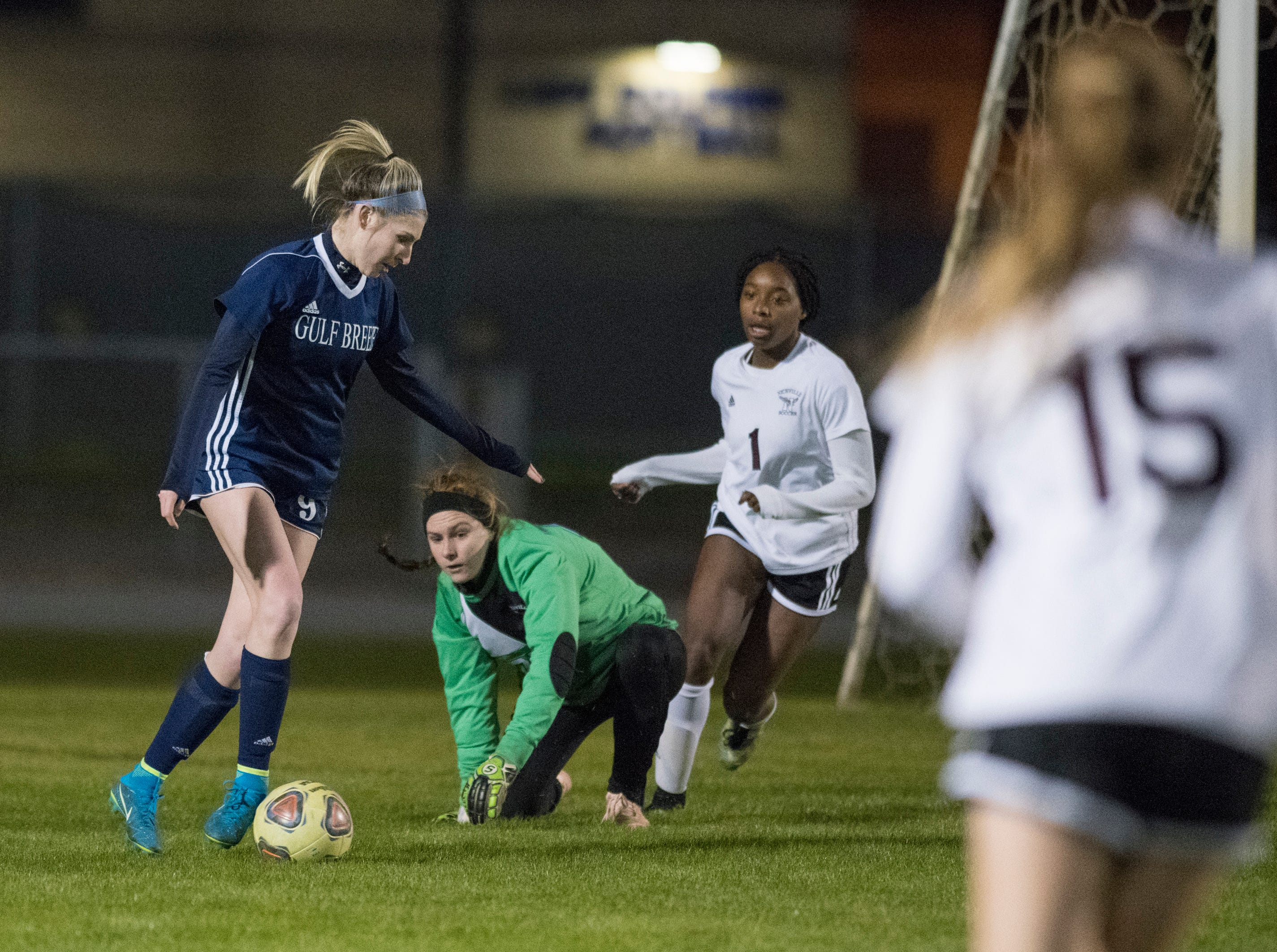 Riley Cassidy (9) dribbles past the Eagles goalie during the Niceville vs Gulf Breeze soccer game at Gulf Breeze High School on Thursday, January 10, 2019.