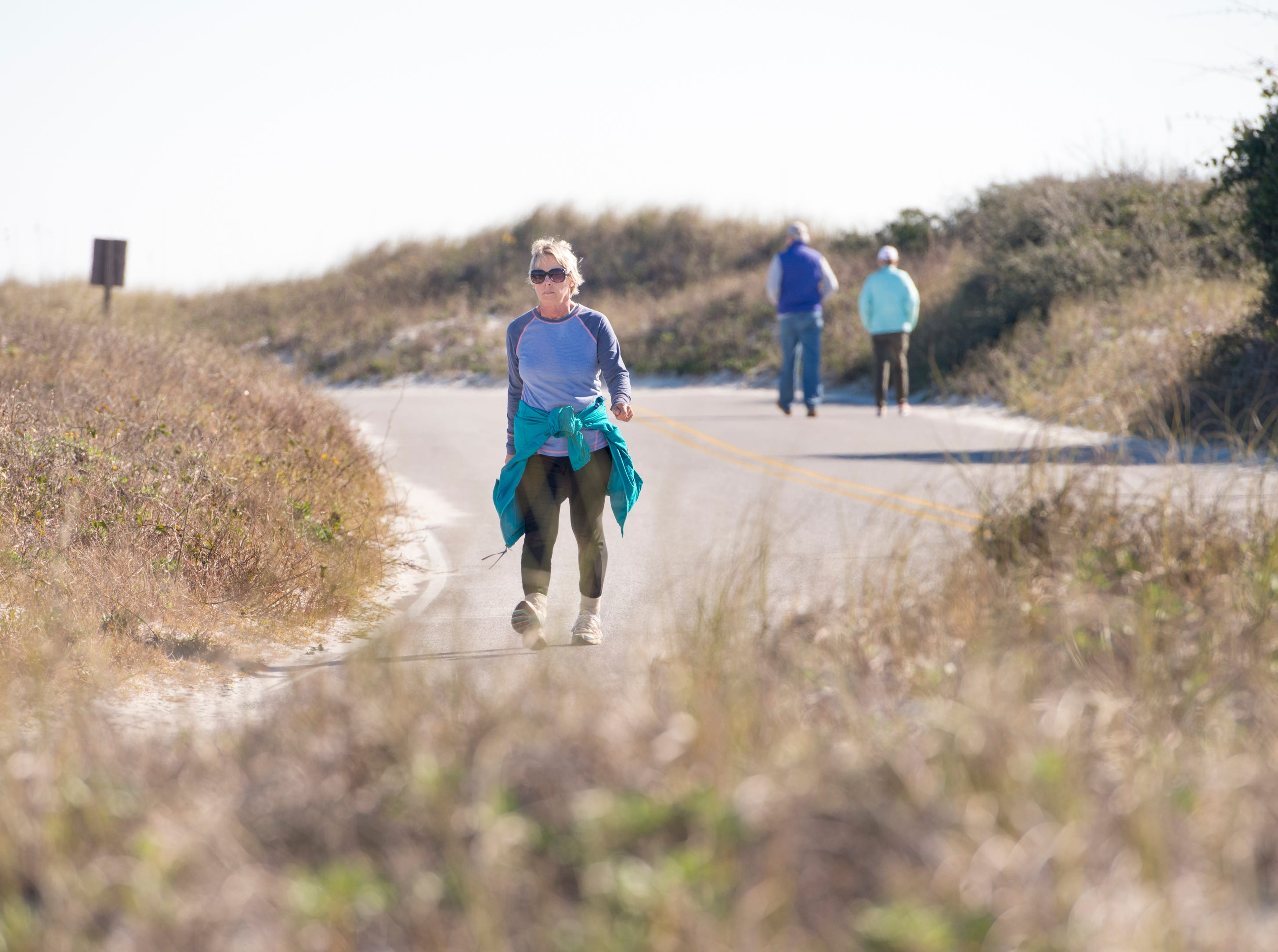 Marcia Ballah, left, walks along the road at Gulf Islands National Seashore's Rosamond Johnson Beach in Perdido Key on Friday, January 11, 2019.  The National Park is closed due to the federal government shutdown.