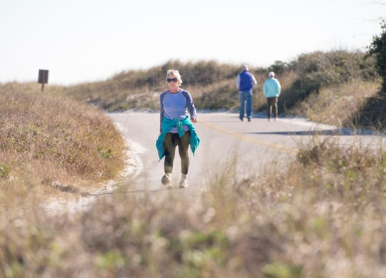 Marcia Ballah, left, walks along the road at Gulf Islands National Seashore's Rosamond Johnson Beach in Perdido Key on Friday. The national park remains closed due to the federal government shutdown.