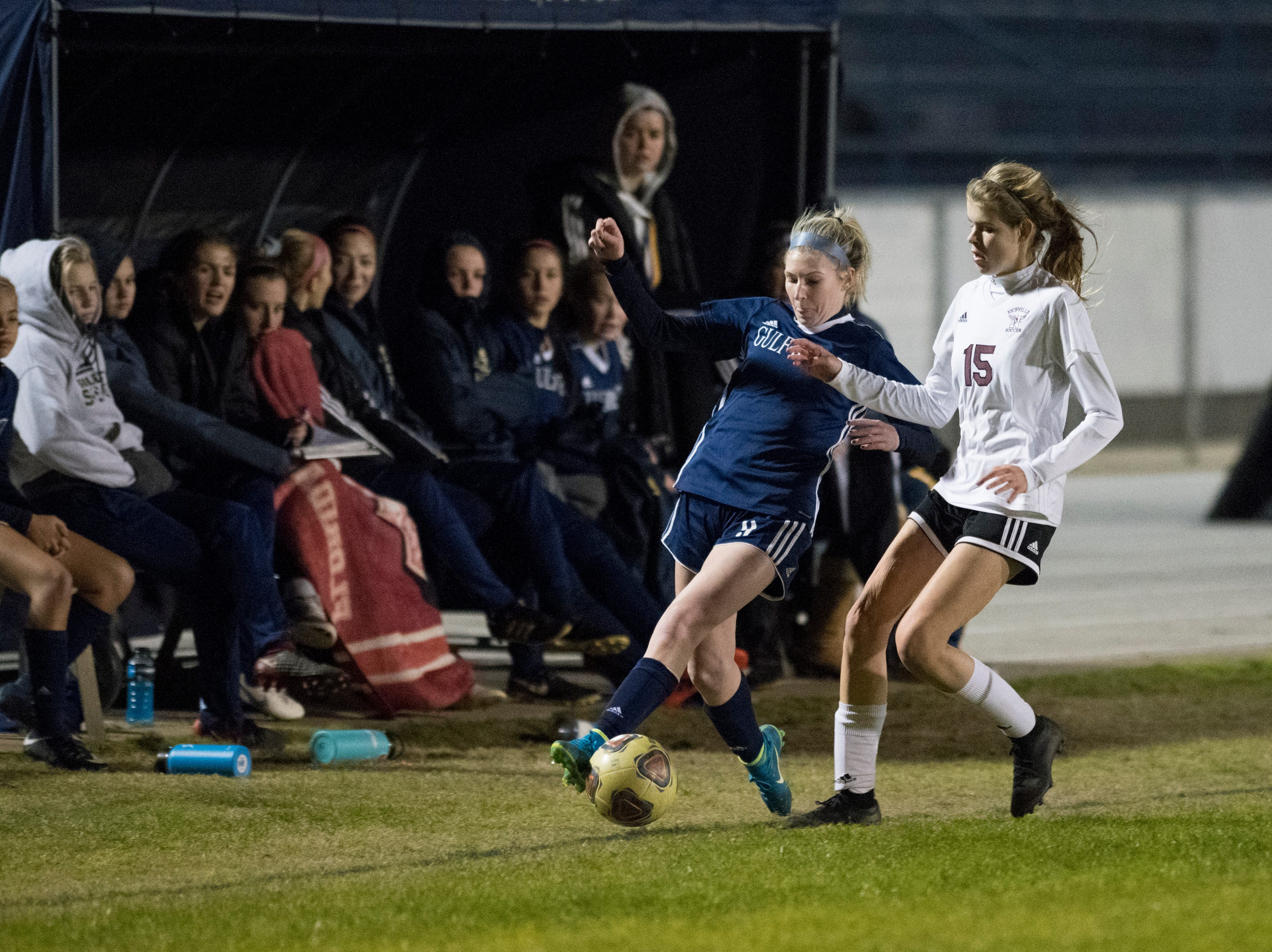 Riley Cassidy (9) and Haley Shelton (15) fight for the ball along the sideline during the Niceville vs Gulf Breeze soccer game at Gulf Breeze High School on Thursday, January 10, 2019.