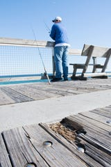 Jonathon Cook, of Navarre, fishes from the pier in Navarre on Friday. The pier is slated to get a major makeover this year, complete with new decking material.