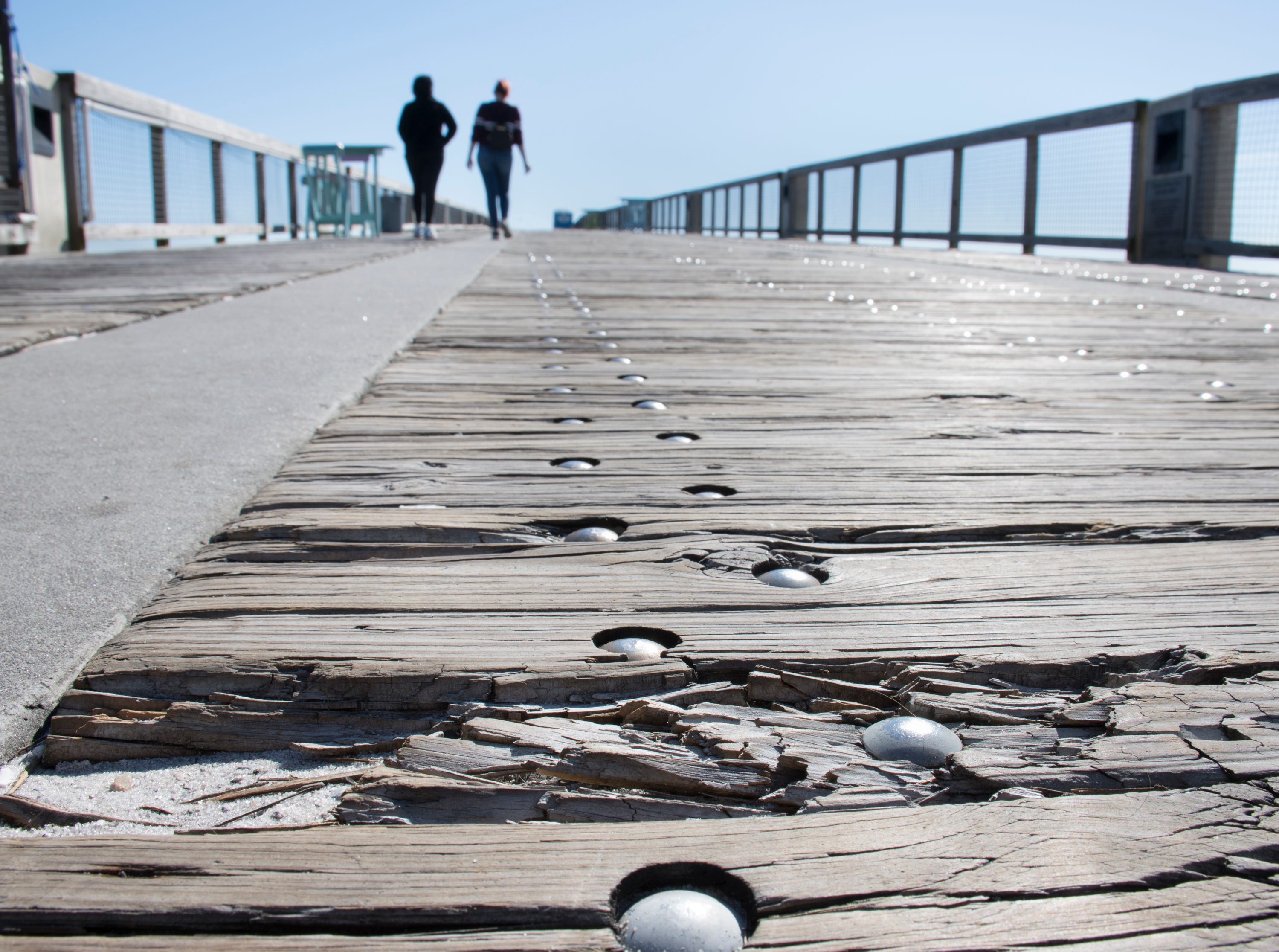 Visitors walk along the pier that is in need of repair in Navarre on Friday, January 11, 2019.  The pier is slated to get a major makeover this year complete with new decking material.