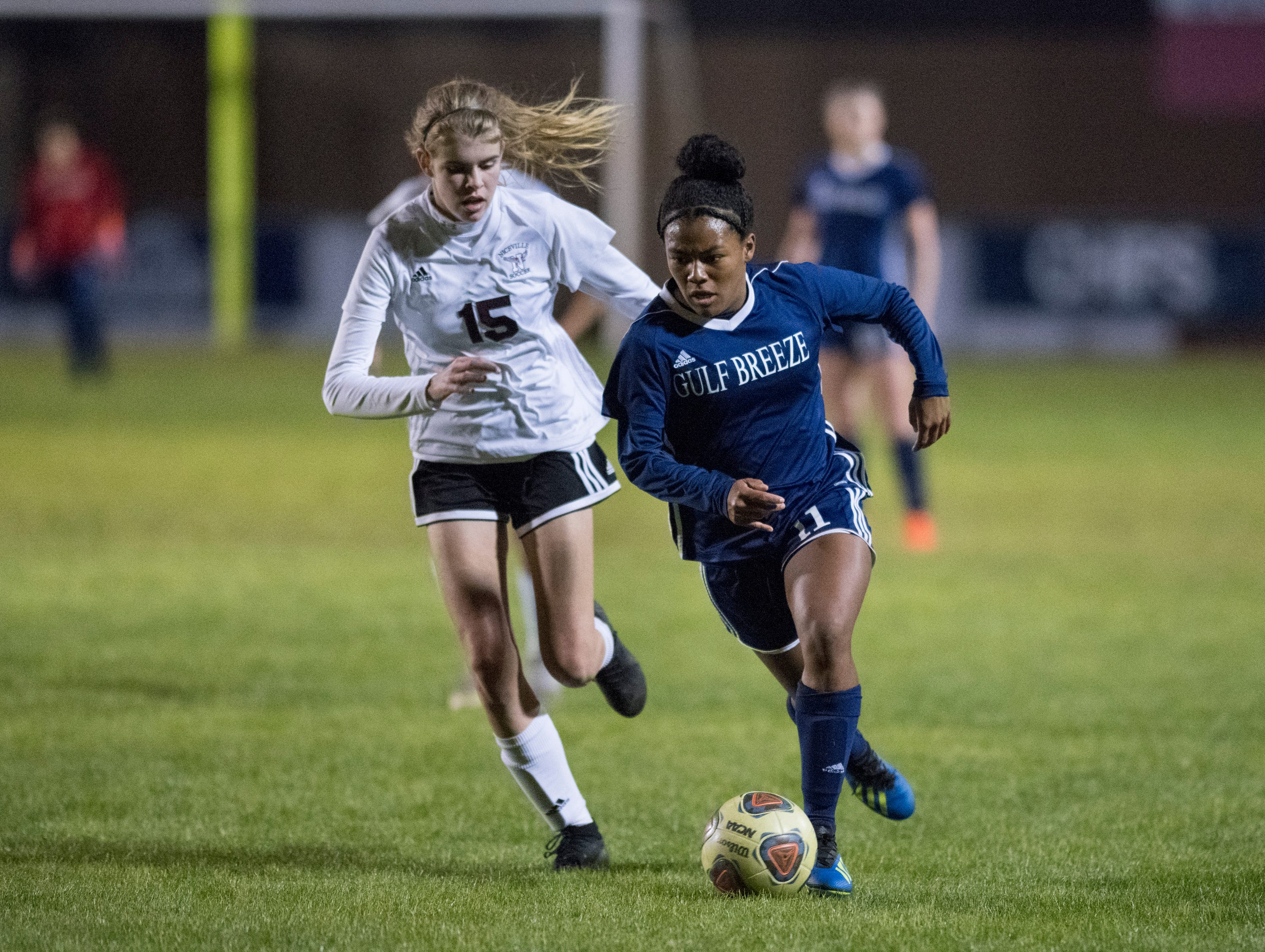 Mya Swinton (11) races past Haley Shelton (15) during the Niceville vs Gulf Breeze soccer game at Gulf Breeze High School on Thursday, January 10, 2019.