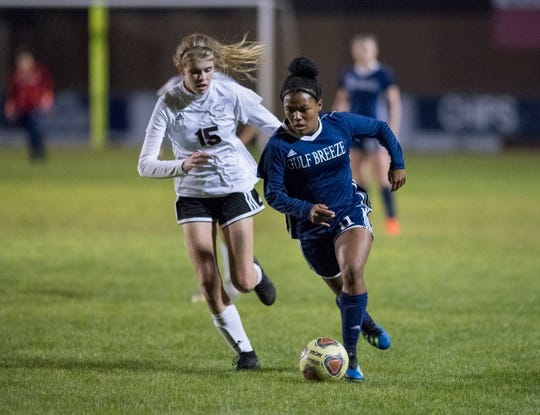 Mya Swinton (11) races past Haley Shelton (15) during the Niceville vs Gulf Breeze soccer game at Gulf Breeze High School on Thursday, January 10, 2019.