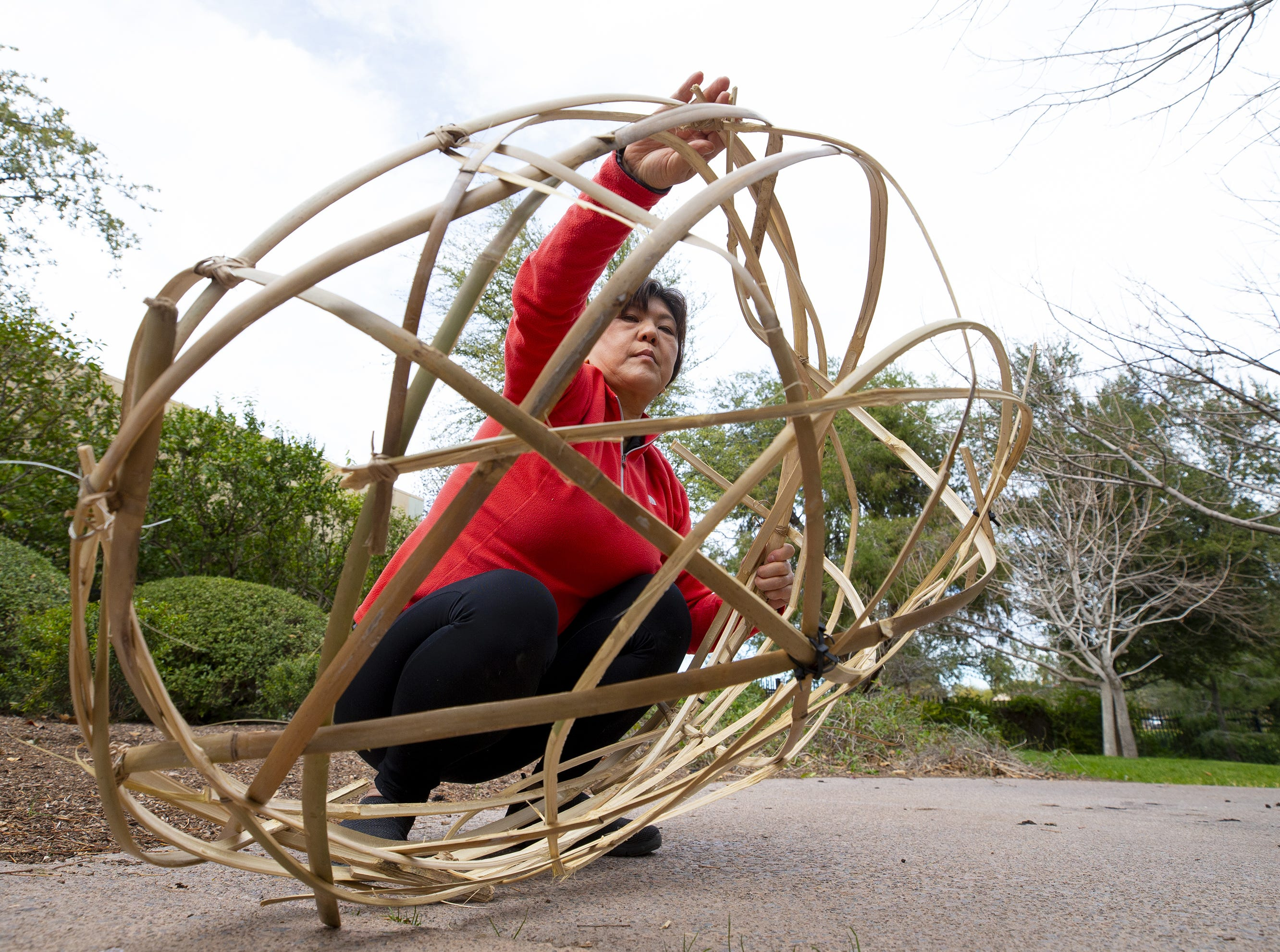 Japanese Friendship Garden art and culture manager Fumiko Katsuta works on a basket for the 10th annual Ikebana exhibit, flowers and their vases.
