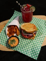 """The Spicoli Burger gets its name from Jeff Spicoli from the film """"Fast Times at Ridgemont High."""" The California-style burger is pictured here with The Closet Vegan's hippy juice, fries and special dipping sauce."""