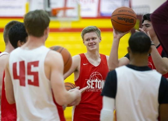 Seton Catholic senior point guard Jackson Lee jokes with his team during practice at the school gym during winter break. Lee is playing basketball without his dad around. His dad, Todd Lee, moved to North Dakota to lead that college basketball team. Jackson is finishing his senior year with his high school friends.