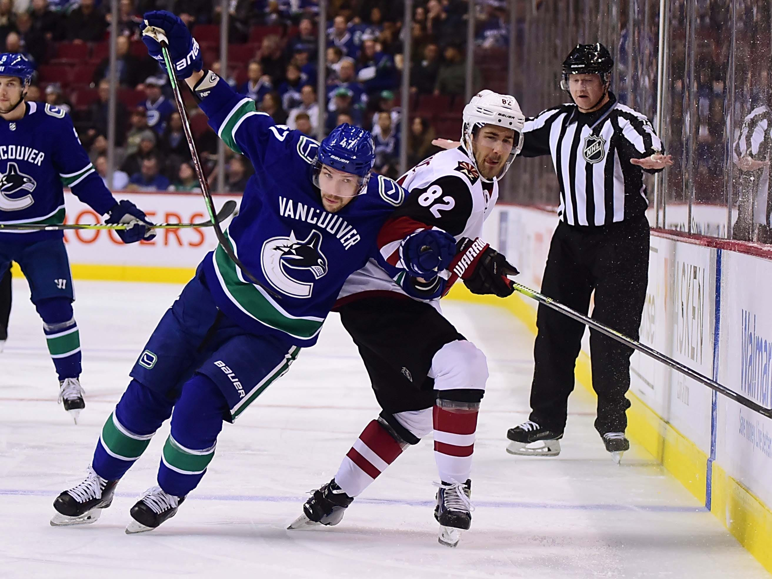 Jan 10, 2019; Vancouver, British Columbia, CAN; Vancouver Canucks forward Sven Baertschi (47) battles for the puck against Arizona Coyotes defenseman Jordan Oesterie (82)  during the first period at Rogers Arena. Mandatory Credit: Anne-Marie Sorvin-USA TODAY Sports