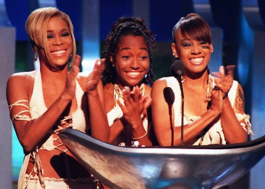 """Tionne """"T-Boz"""" Watkins (L), Rozonda """"Chilli"""" Thomas and Lisa """"Left Eye"""" Lopes of the group TLC celebrate their award for Best R&B Video at the 1995 MTV Video Music Awards held at Radio City Music Hall in New York. The award was for their """"Waterfalls"""" video and TLC also won two other awards."""