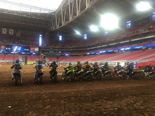 Monster Energy AMA Supercross racers practice on the track at State Farm Stadium.