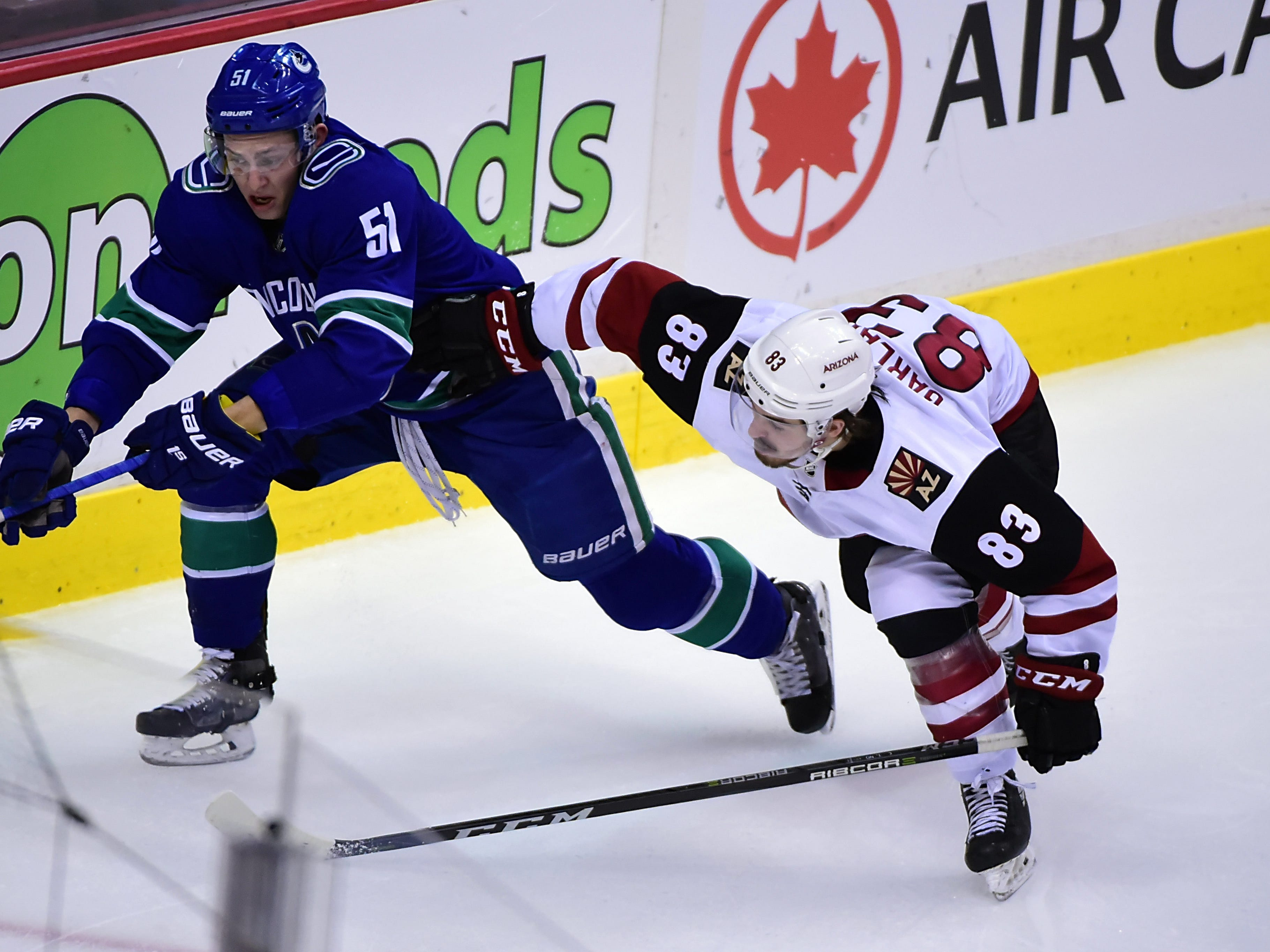 Jan 10, 2019; Vancouver, British Columbia, CAN; Arizona Coyotes forward Conor Garland (83) reaches for the puck against Vancouver Canucks defenseman Troy Stecher (51) during the second period at Rogers Arena. Mandatory Credit: Anne-Marie Sorvin-USA TODAY Sports