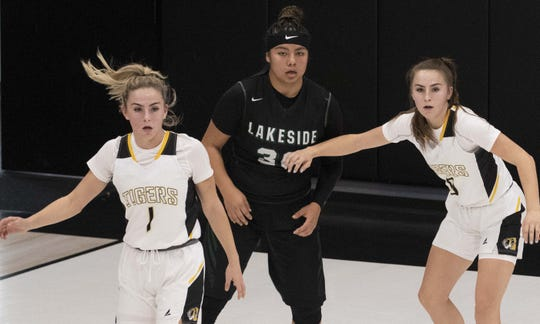 Gilbert High School basketball players Haley Cavinder, on left and her twin sister Hanna Cavinder on far right, defends Lakeside Jolene Armendariz during the Nike Tournament of Champions in Phoenix, Az.
