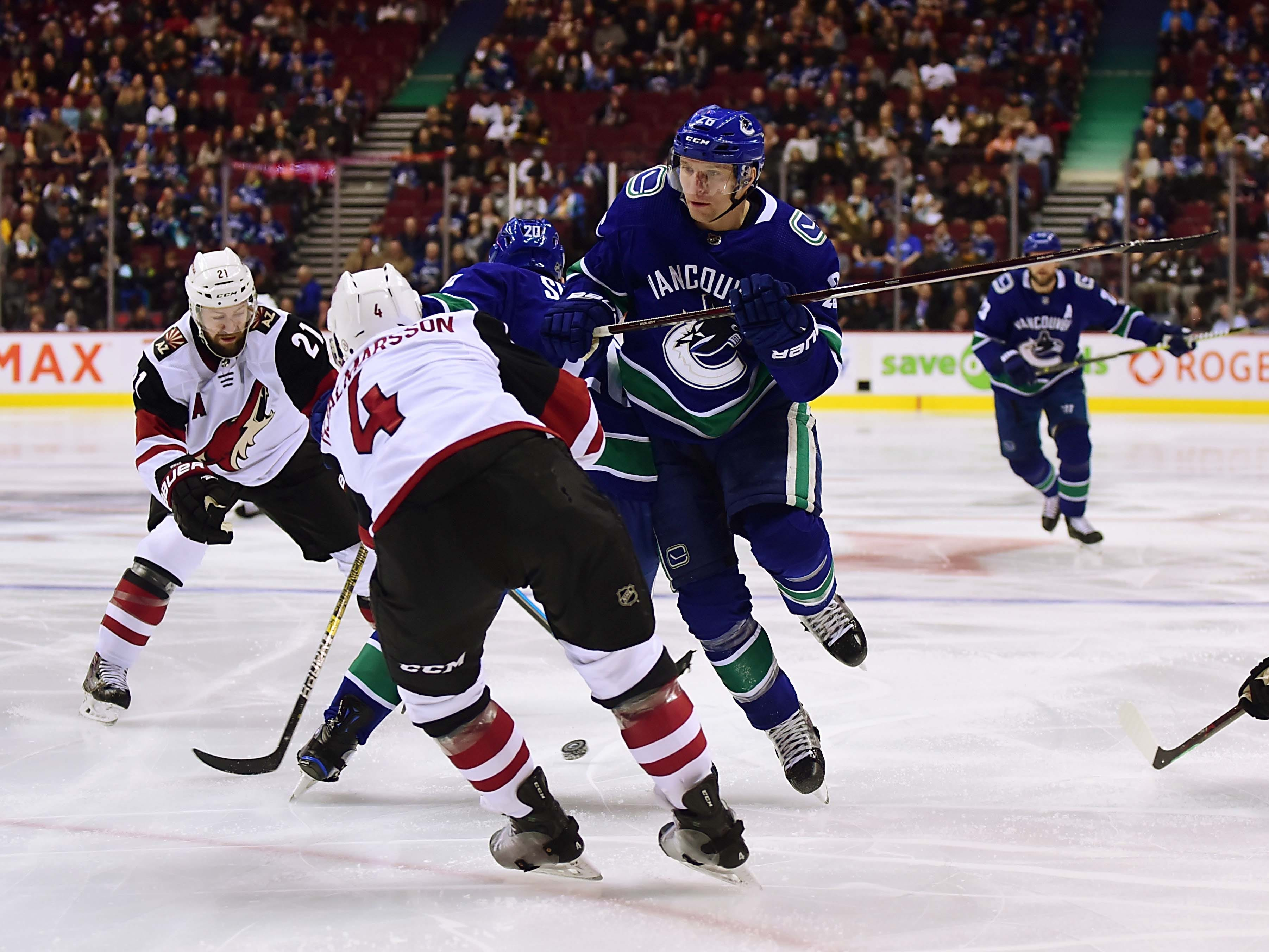 Jan 10, 2019; Vancouver, British Columbia, CAN;  Vancouver Canucks forward Antoine Roussel (26) jumps over Arizona Coyotes defenseman Niklas Hjalmarsson (4) during the first period at Rogers Arena. Mandatory Credit: Anne-Marie Sorvin-USA TODAY Sports