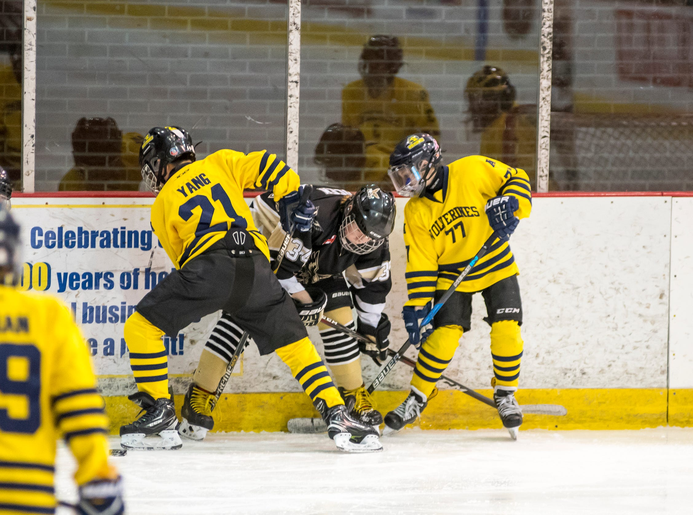 Ann Arbor Wolverines defenseman Anthony Yang (21) and forward Ryan Naughton (77) hold Quinte West Hawks forward Trey Cocek against the wall as they fight for the puck during their Silver Stick Finals PWA match Thursday, Jan. 10, 2019 at McMorran Arena.