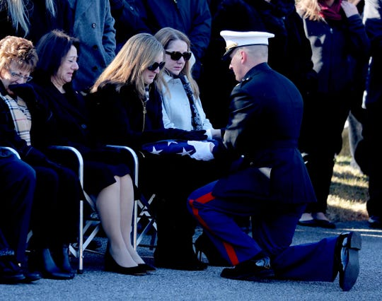 Erica Brophy, widow of U.S. Marine Corps Major James Brophy, is presented the American flag that draped her husband's casket during a burial at the Poughkeepsie Rural Cemetery Jan. 11, 2018. The burial followed a funeral service at the Majed J. Nesheiwat Convention Center in Poughkeepsie. Brophy was killed in a collision of two military planes off the coast of Japan in December.