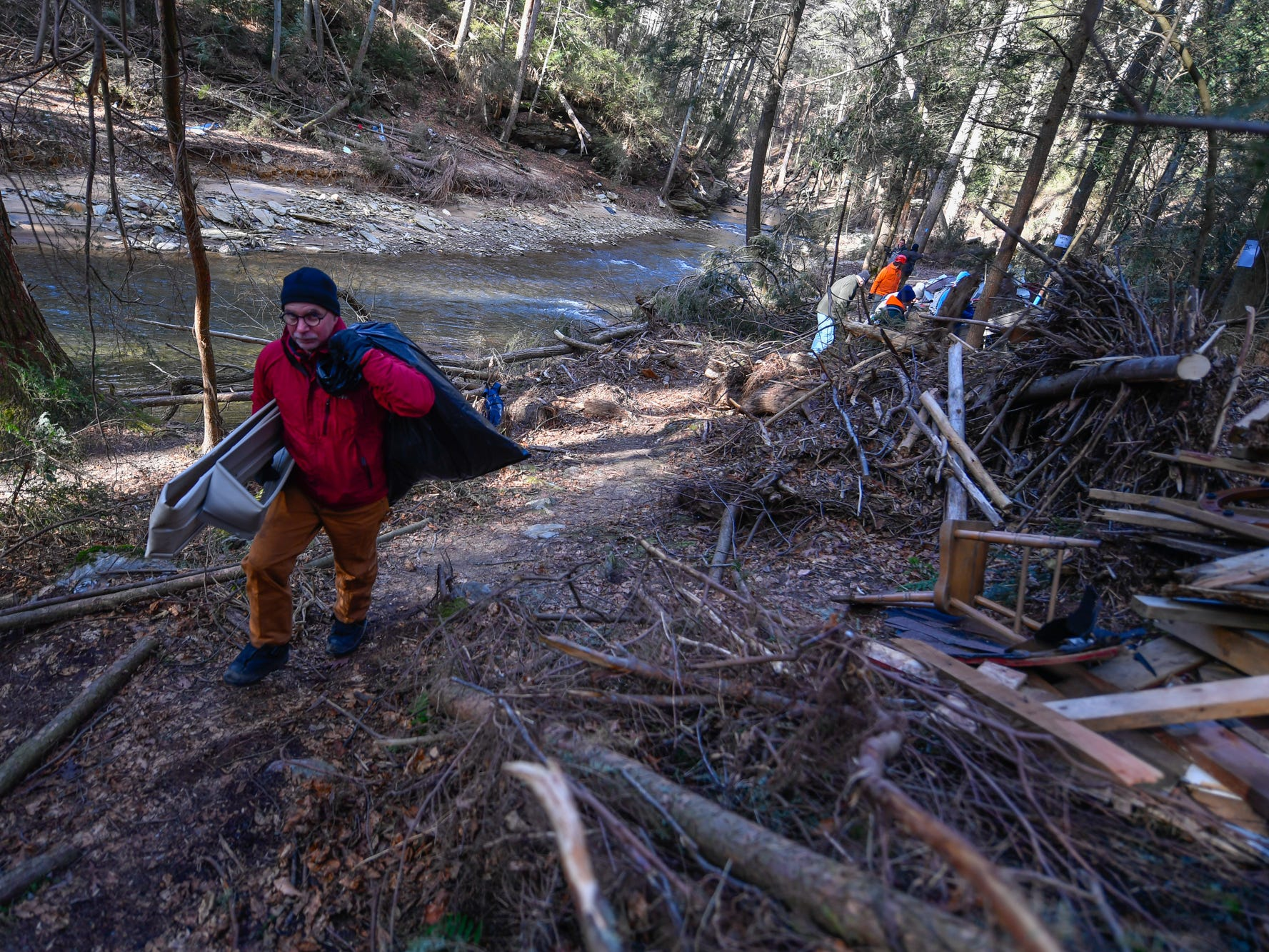 Volunteer Mark Kaiser of Lancaster hauls out debris from August flooding along Otter Creek in Airville, Thursday, January 10, 2019.