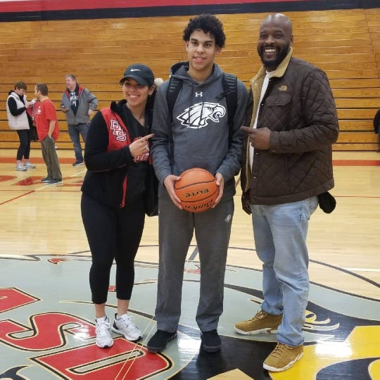 Elijah Sutton poses with his sister, Maya, and brother, Sam, after scoring his 1,000th career point at Dover High School. Sutton reached the mark by scoring 42 points against Donegal on Jan. 3.