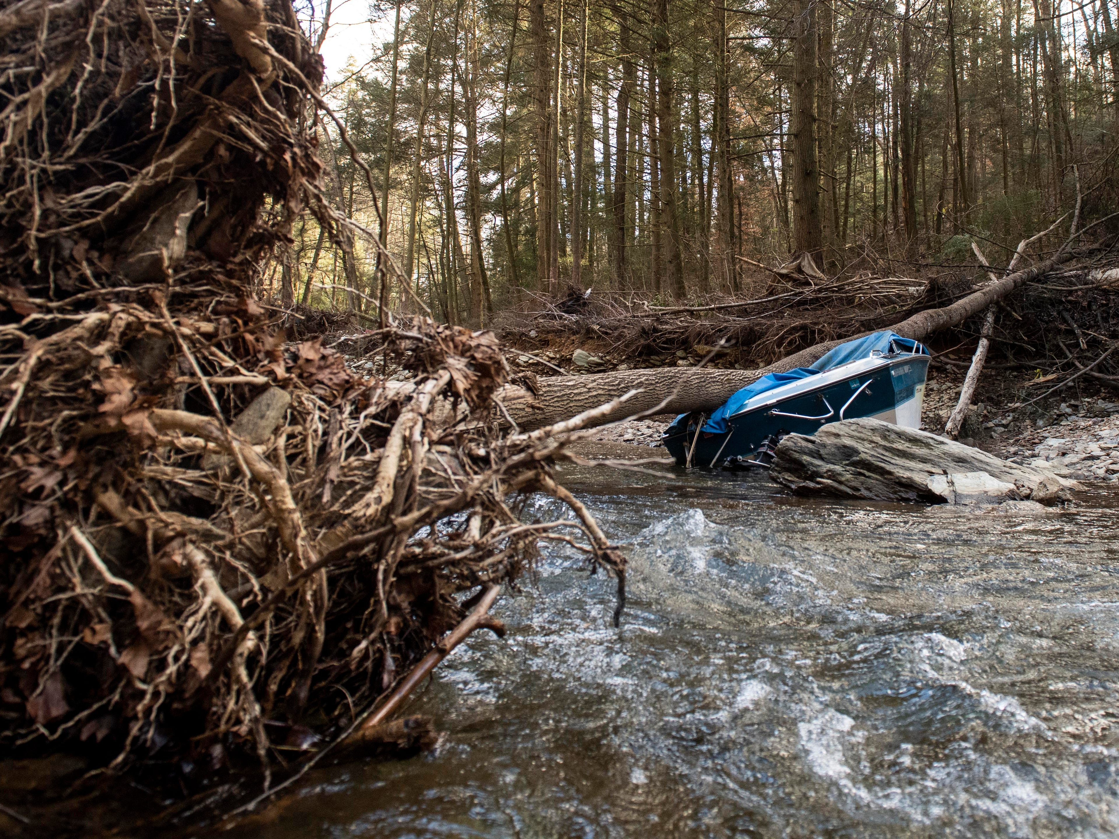 A boat, crushed by a downed tree, is one of a few large, heavy objects that the Lancaster County Conservancy is still trying to figure out how to get out of the creek, Thursday, Jan. 10, 2019. Flooding that ravaged many parts of York County in Aug. 2018 swept debris into Otter Creek, in Airville.