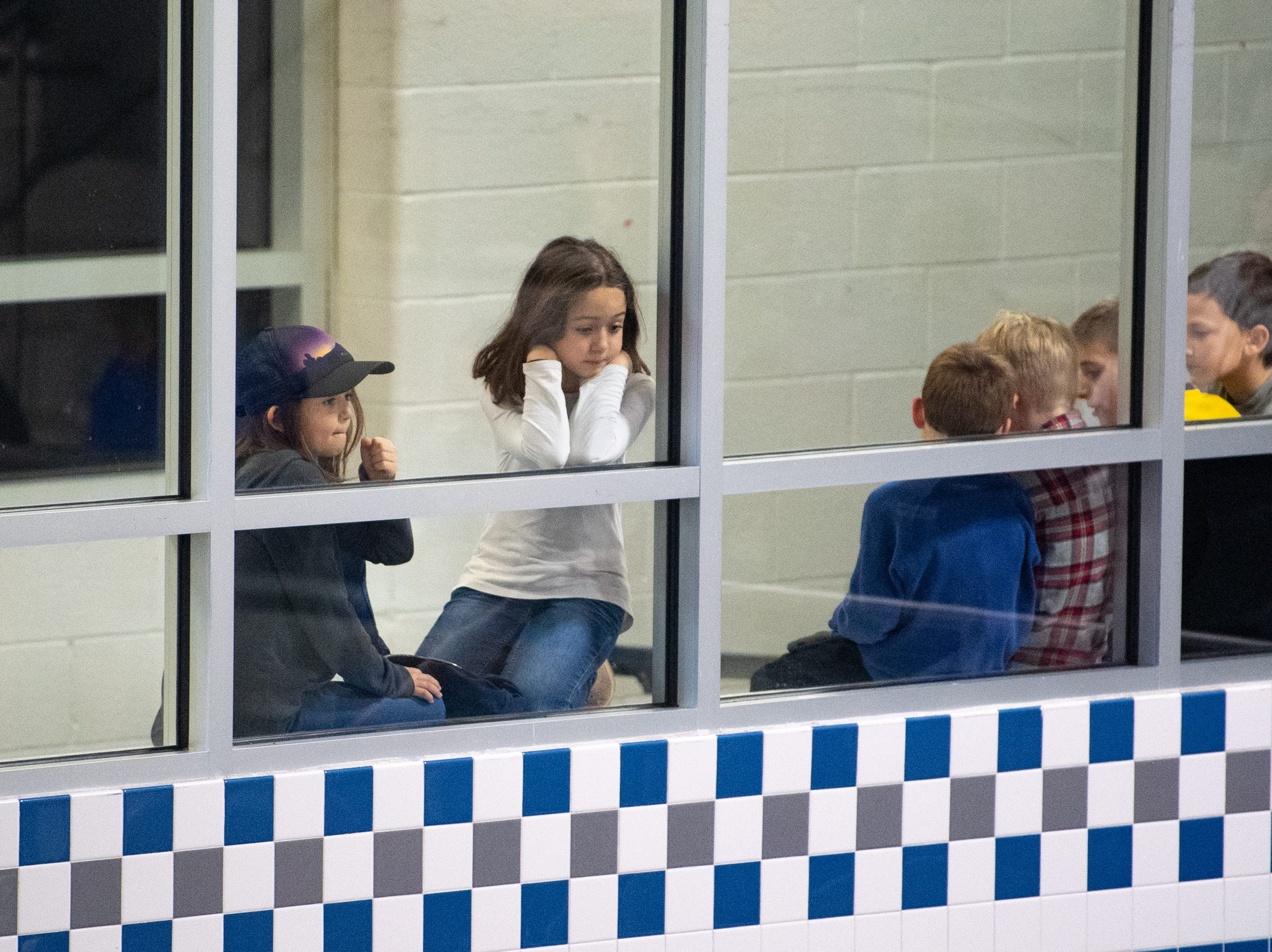 Fans watch the meet through the window outside of the pool area during the boys' and girls' swim meet between Dallastown and Central York at Dallastown Area High School, January 10, 2019. The Panthers defeated the Wildcats 93 to 77 and the Lady Panthers defeated the Lady Wildcats 96 to 74.