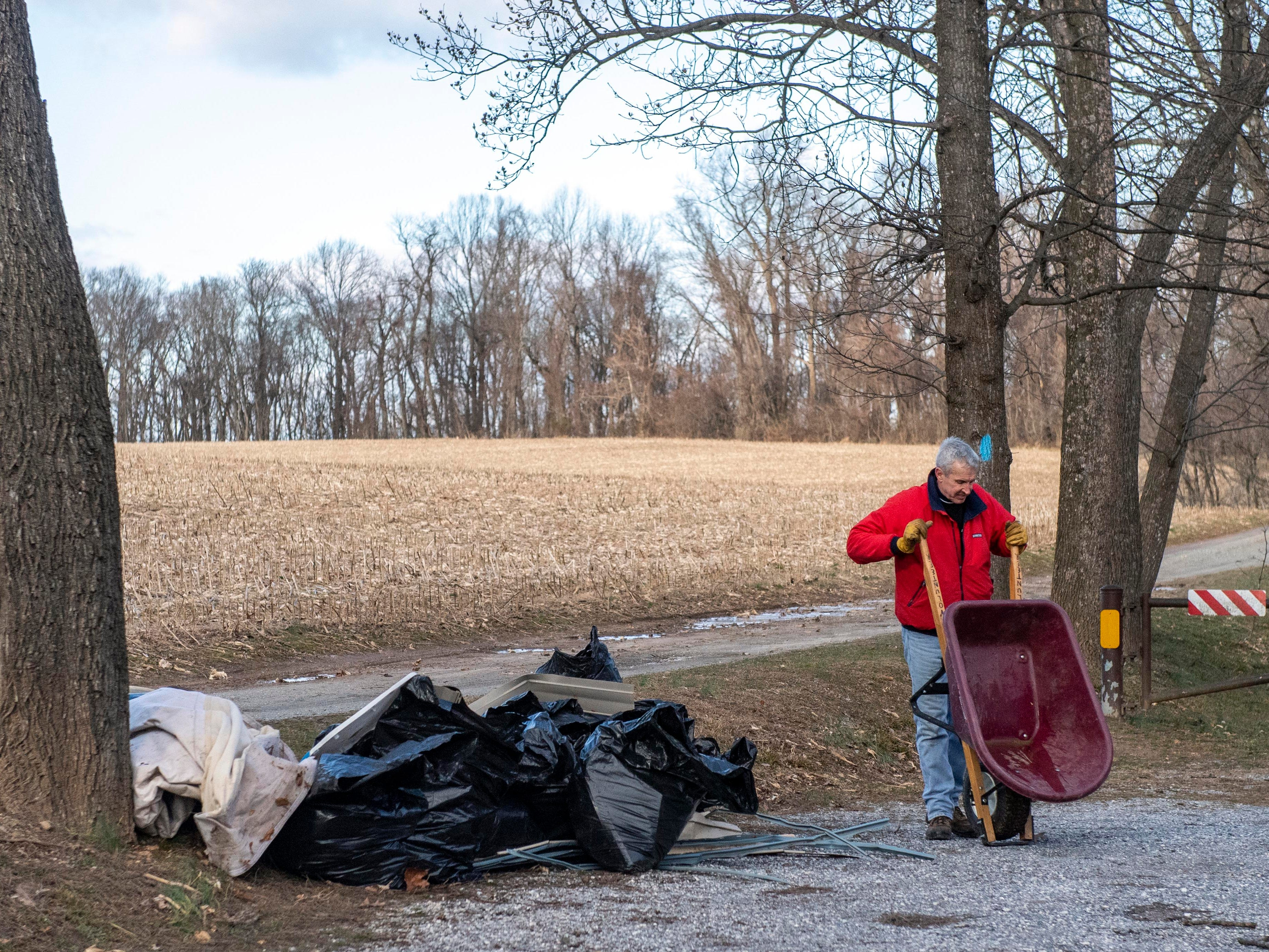 Steve Smith, a volunteer who has been removing trash and debris since the 8:30 a.m., empties his wheelbarrow in the parking lot of Urey Overlook, Thursday, Jan. 10, 2019. Flooding that ravaged many parts of York County in Aug. 2018 swept debris into Otter Creek, in Airville.