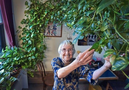 "In this Tuesday, Jan. 8, 2018 photo, Gabrellen ""Gabby"" Pfarr, poses in her Lancaster, Pa. home, along with her beloved houseplant. Pfarr, who's dying of cancer, is trying to find a home for her 15-foot-long plant."