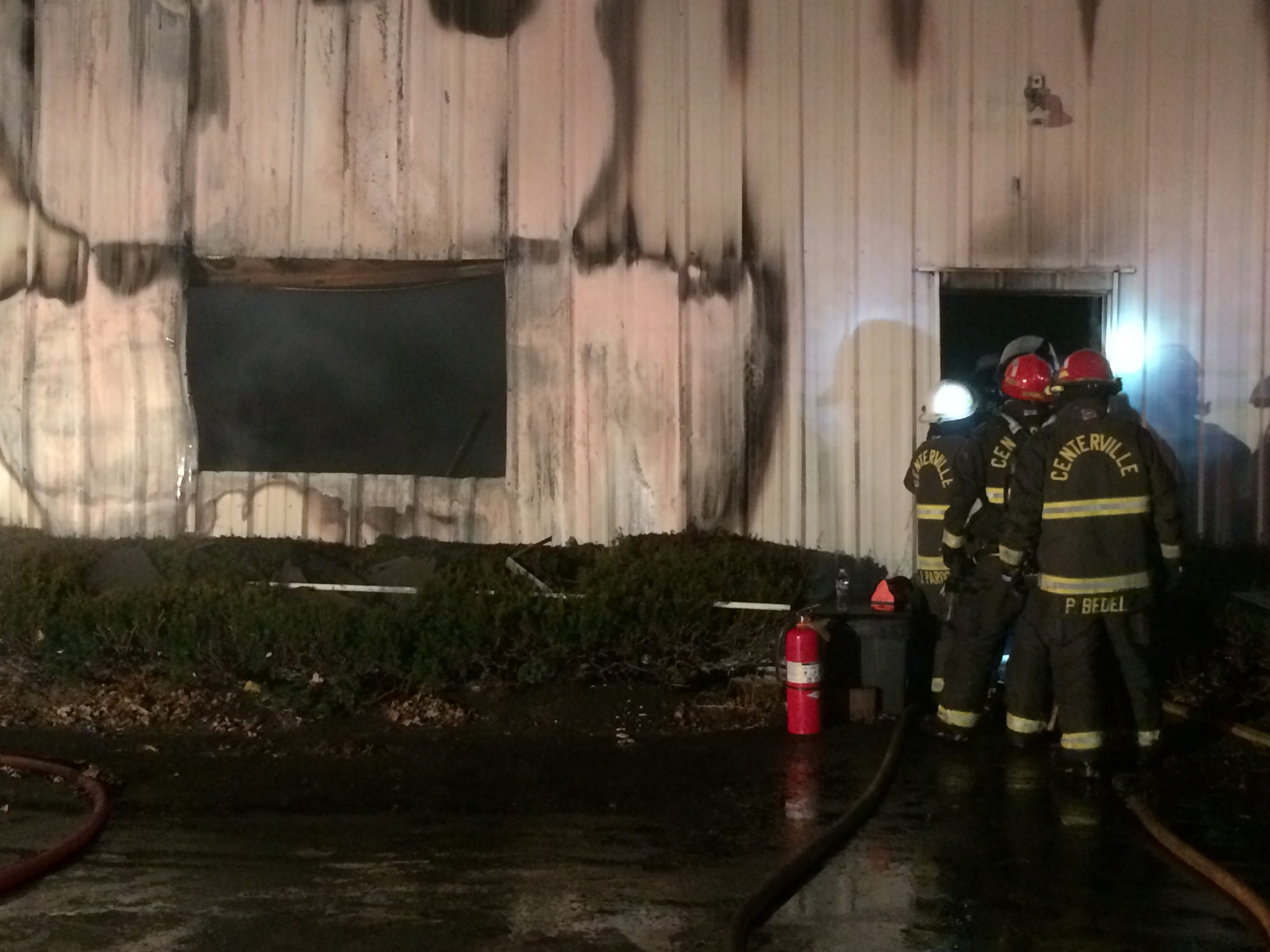 Firefighters try to extinguish hot spots from a doorway Thursday night at Red Diamond Diesel repair shop.