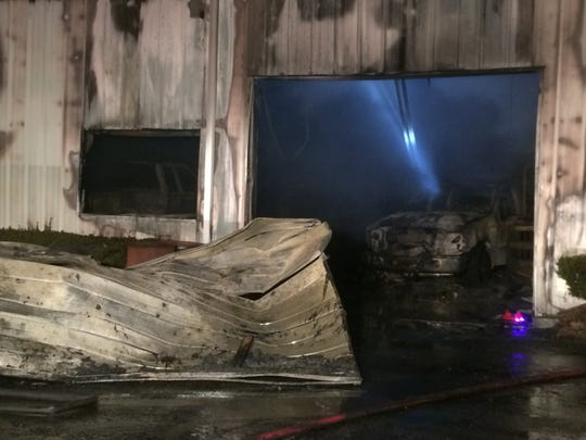Burned vehicles sit inside the Red Diamond Diesel repair shop Thursday night after a fire destroyed the building.